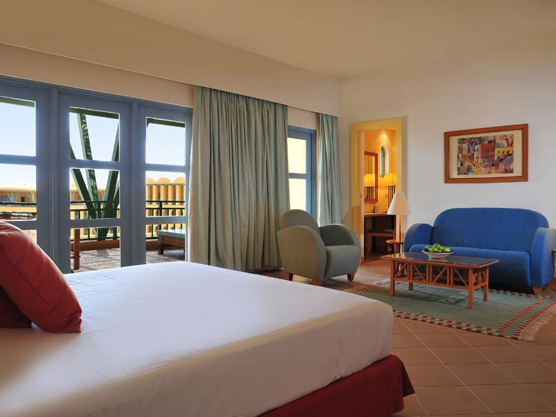 king bed at standard room with seating area and balcony view to the hotel area at strand beach resort taba heights