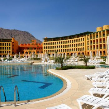 a side view of strand beach resort taba heights with pool area and mountains view