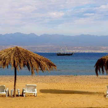 beach area with seating and a view of red sea mountains at strand beach resort taba heights