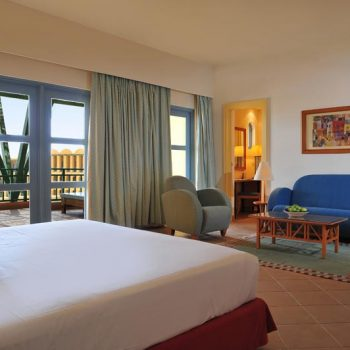 standard room with bed and seating area and balcony view at strand beach resort taba heights
